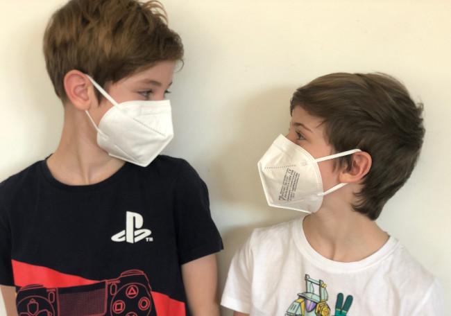 Man sieht zwei Jungen mit FFP2 Maske