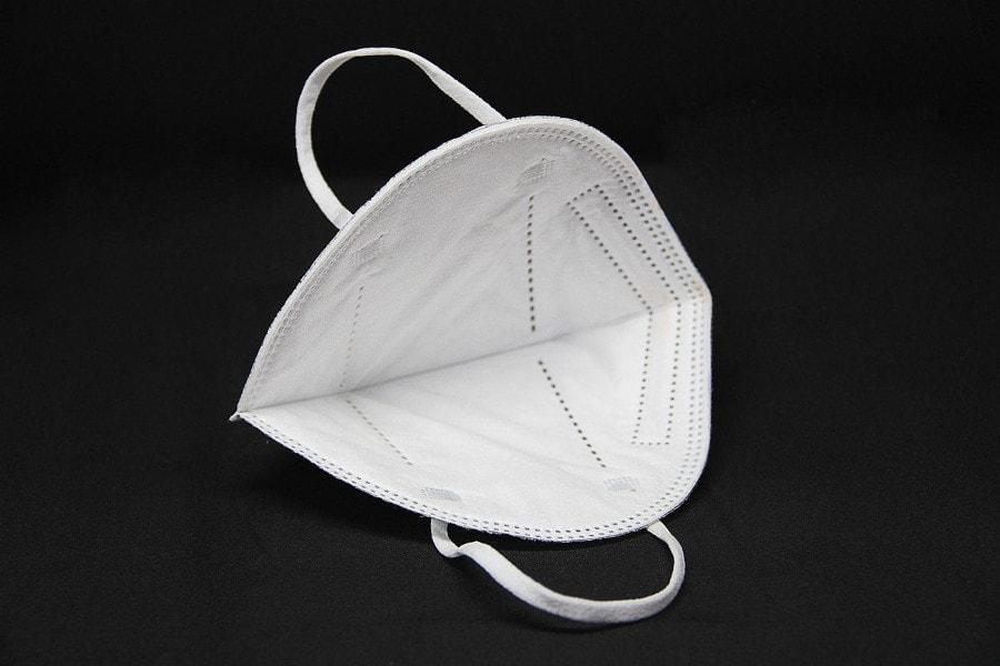 Zu sehen ist eine Atemschutzmaske, auf der keine CE-Kennzeichnung zu sehen ist. Die Maske wird von Viren umgeben.