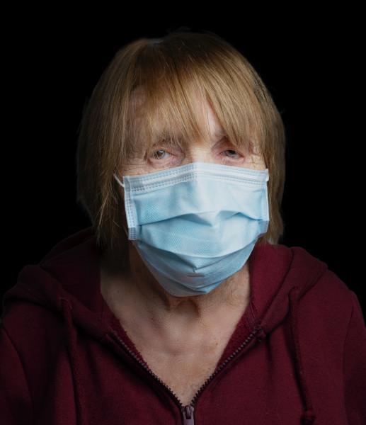 Eine ältere Frau mit Maske passt ihrem Mann, der Hörgeräteträger ist, die Maske an.