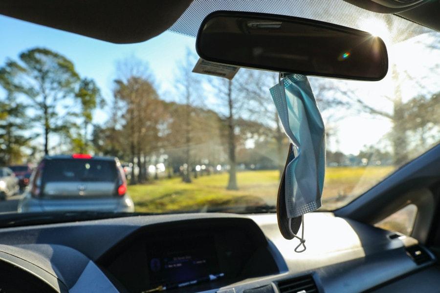Zu sehen ist eine blaue OP-Maske, die am Rückspiegel im Auto hängt.