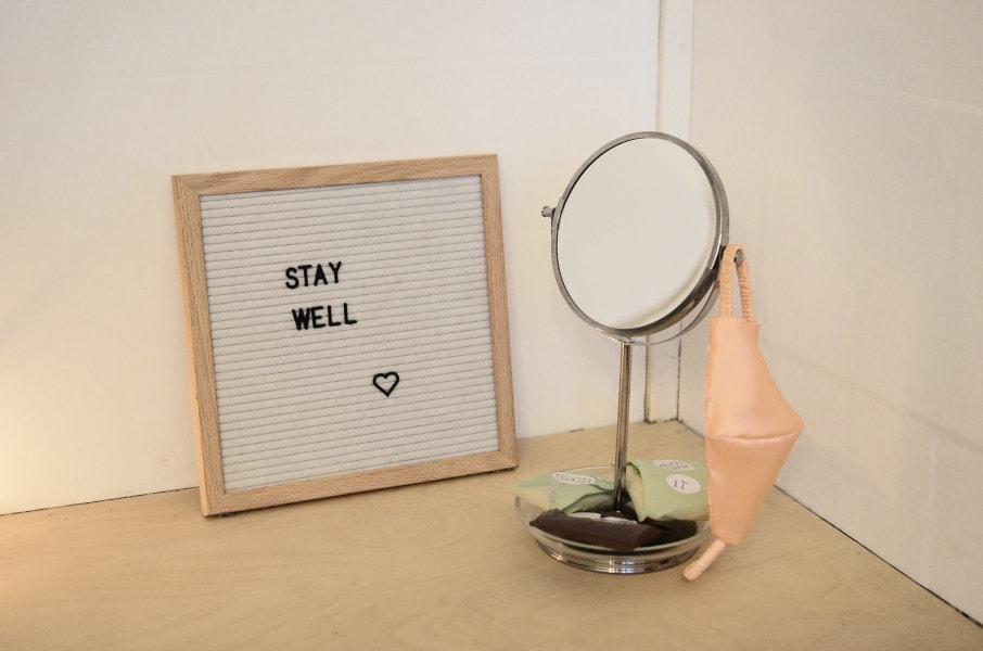"""Zu sehen ist ein Spiegel, an dem eine Maske hängt, dahinter steht ein Letterboard mit der Aufschrift """"Stay Well""""."""