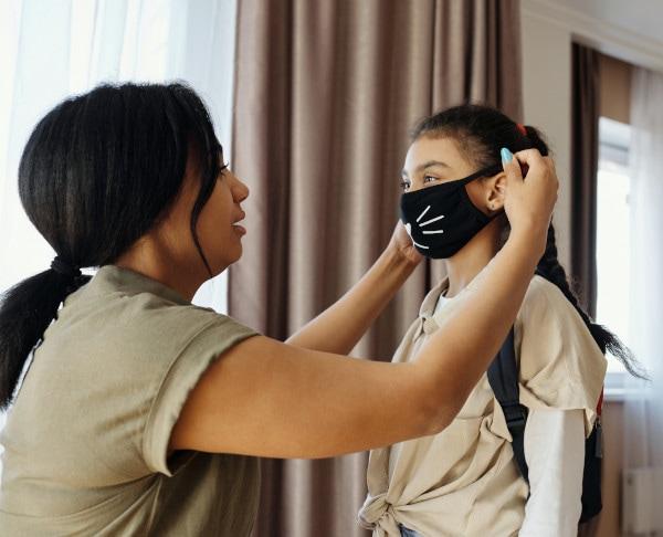 Zu sehen ist eine Frau, die ihrer Tochter eine Maske aufsetzt.