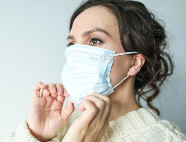 Zu sehen ist eine Frau, die eine OP-Maske an ihr Gesicht anpasst.