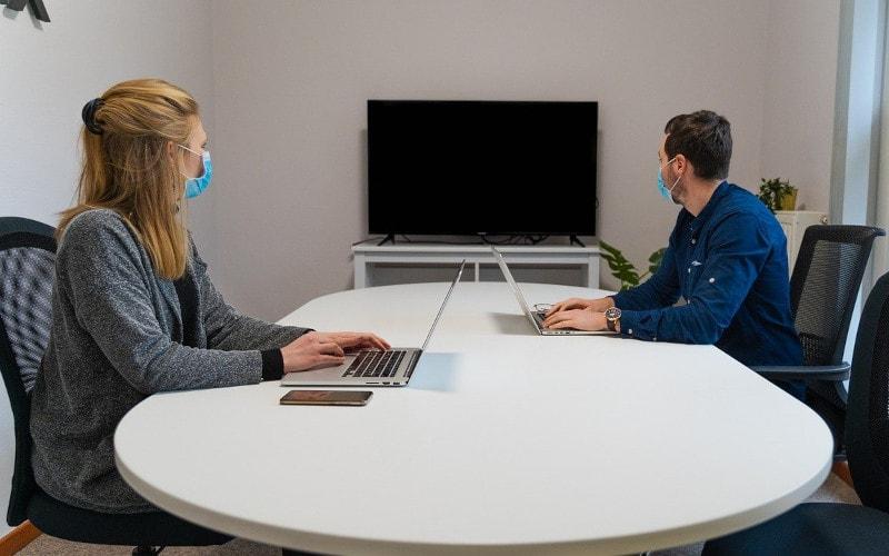 Zwei Arbeitskollegen, eine Frau und ein Mann, sitzen mit Abstand zueinander und mit Masken in einem Meetingraum.