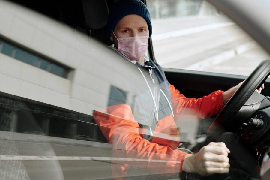 Zu sehen ist ein Mann am Steuer, der wegen der Maskenpflicht im Auto eine rosafarbene OP-Maske trägt.
