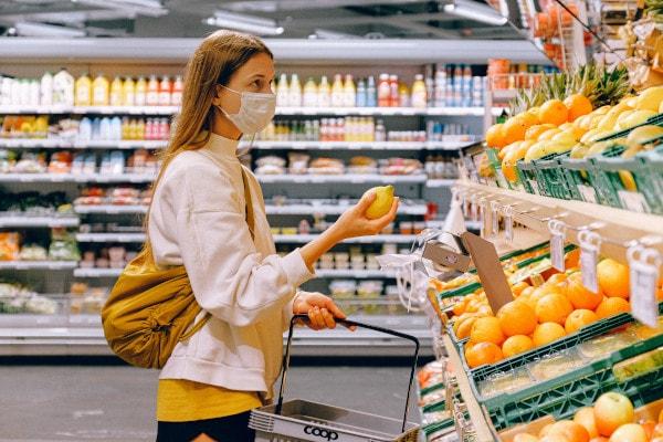 Zu sehen ist eine junge Frau mit OP-Maske in der Obstabteilung im Supermarkt.
