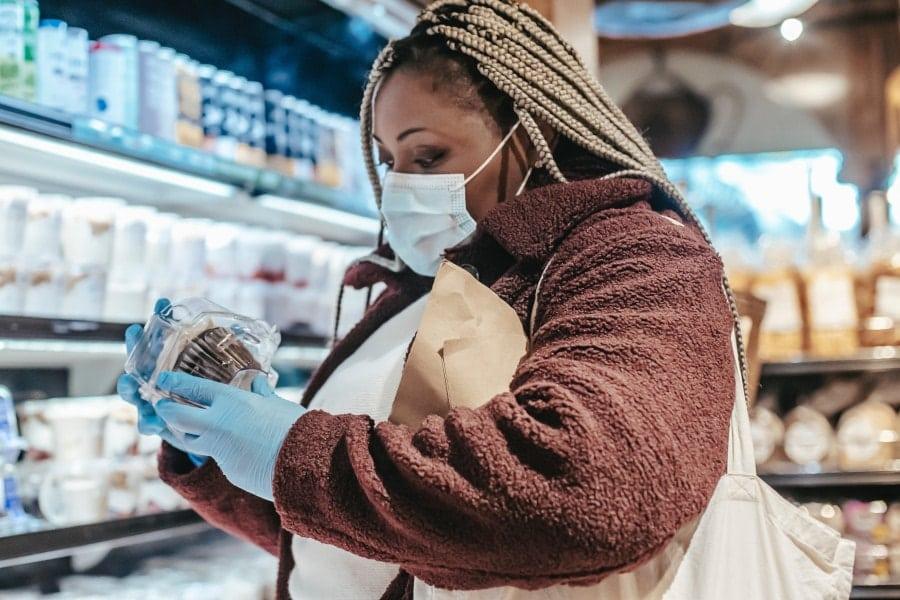 Zu sehen ist eine Frau, die beim Einkaufen eine Maske trägt.