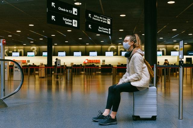 Zu sehen ist eine Frau am Flughafen, die eine OP-Maske trägt und auf Ihrem Koffer sitzt